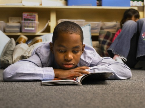 Boy Reading Book in Classroom